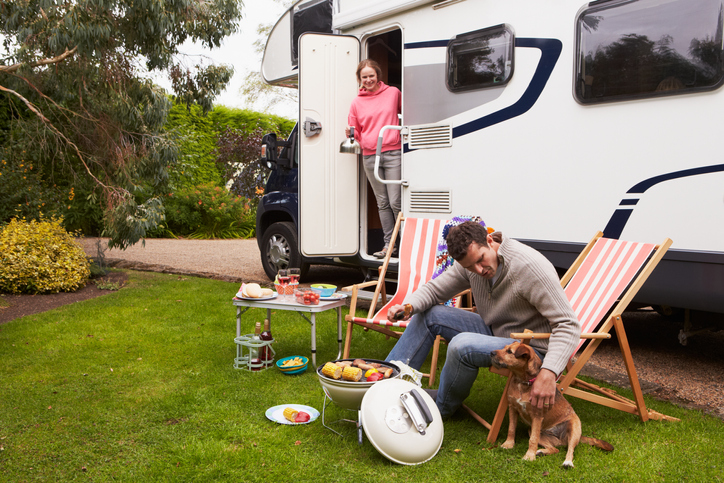New Couple In RV Enjoying Barbeque On Camping Holiday