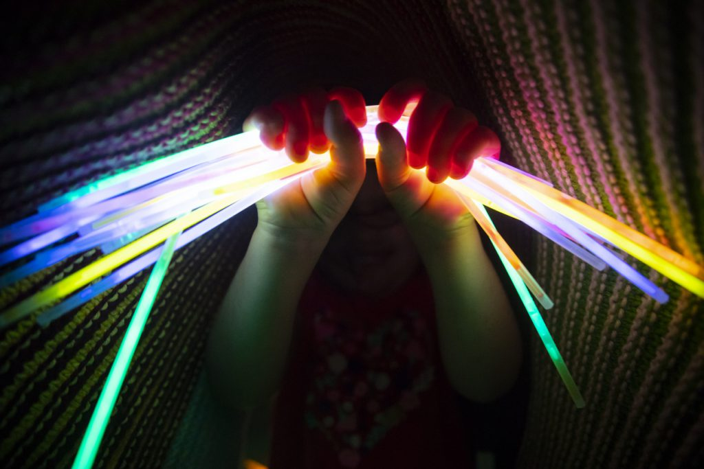 camping on a budget girl holding glow sticks