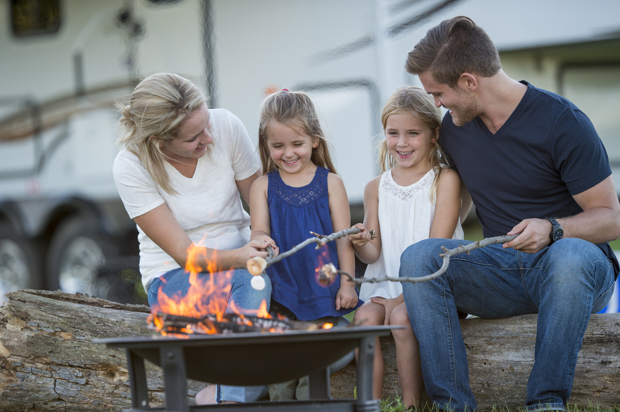 camping on a budget family roasting marshmellows