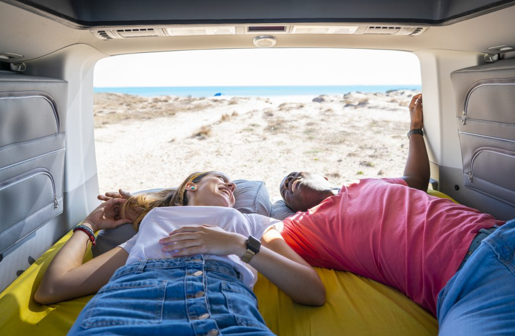 Environmentally friendly RVing - couple laying in RV by the beach