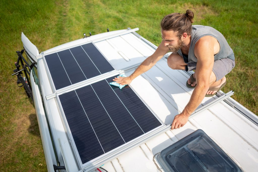Environmentally Friendly RVing - man on roof of RV cleaning solar panels