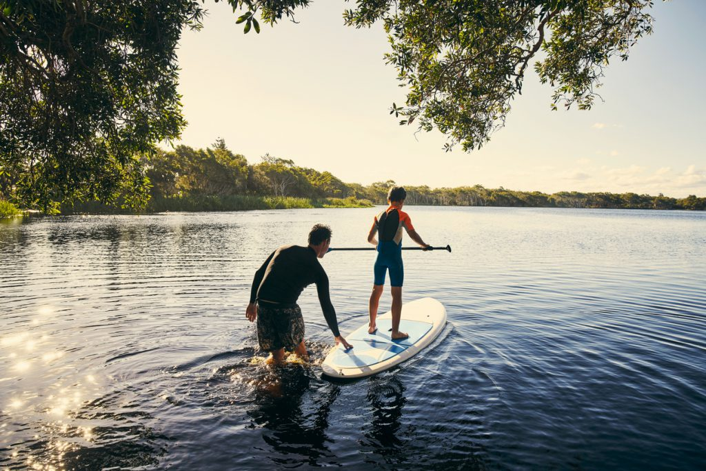 most important things to keep in your RV - father helping son out on paddleboard