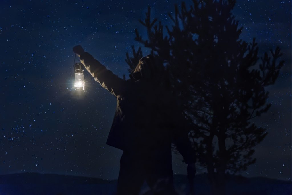 most important things to keep in your RV - man holding a lantern at night