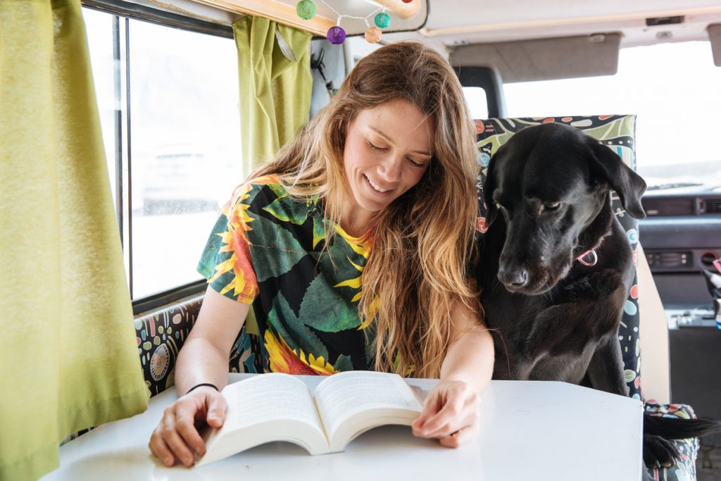 RV with dogs happy young woman reading a book and playing with her dog in a camper van