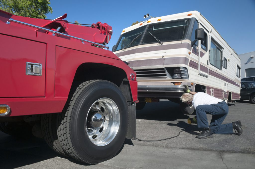 RV Emergency Kit - A tow truck driver preparing a broken down RV for towing.