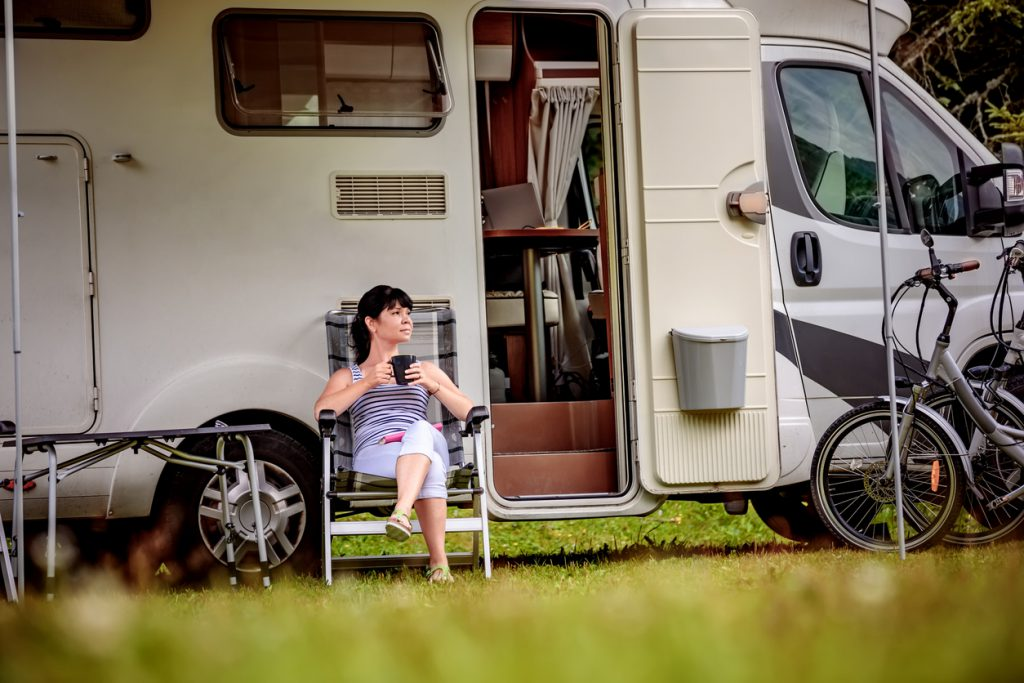 Woman is standing with a mug of coffee near the camper. Caravan car Vacation. Family vacation travel, holiday trip in motorhome RV