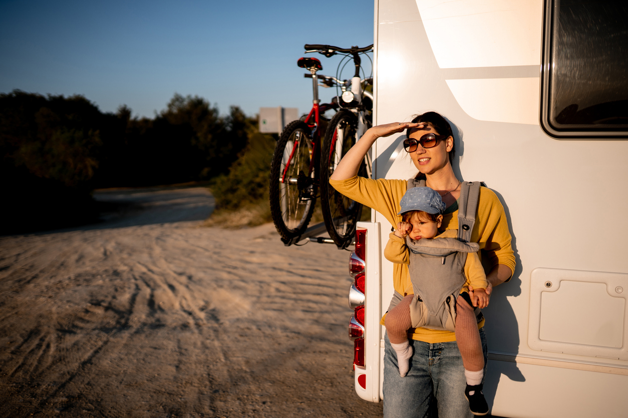 RVing with a baby - Young mother standing with her daughter in a front of motor home, and looking on view