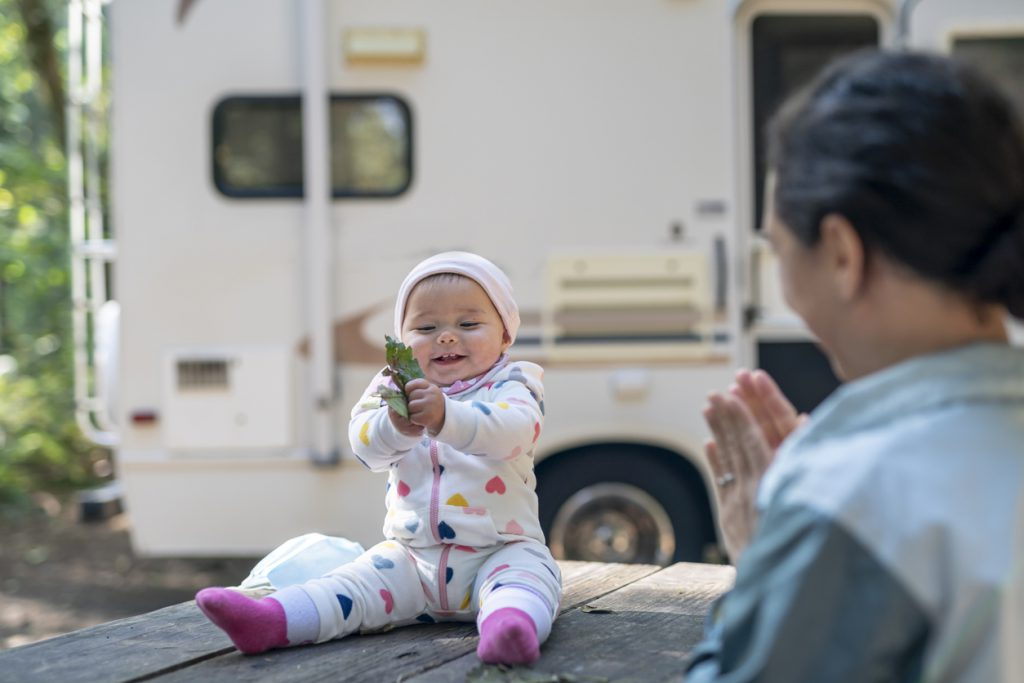 RVing with a baby - A young mother plays with her smiling baby girl who is holding a leaf while sitting on top of a picnic table. The family is camping and a motor home is in the background.