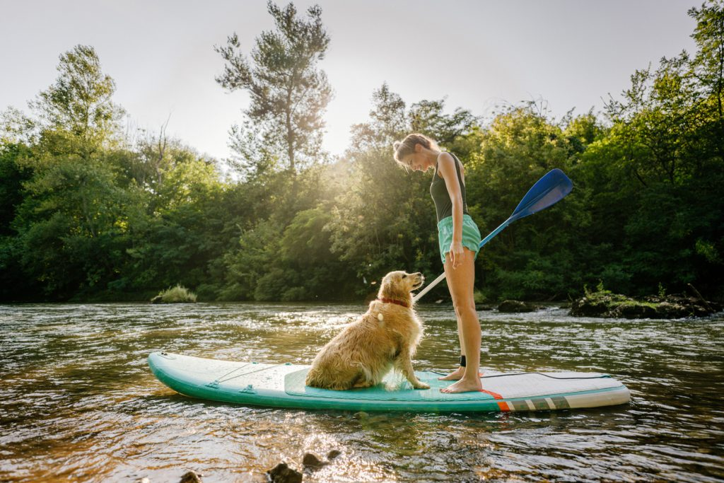 Photo of a young woman and her dog stand up paddling on the river; enjoying the beautiful, warm summer afternoon, far from the hustle of the city.