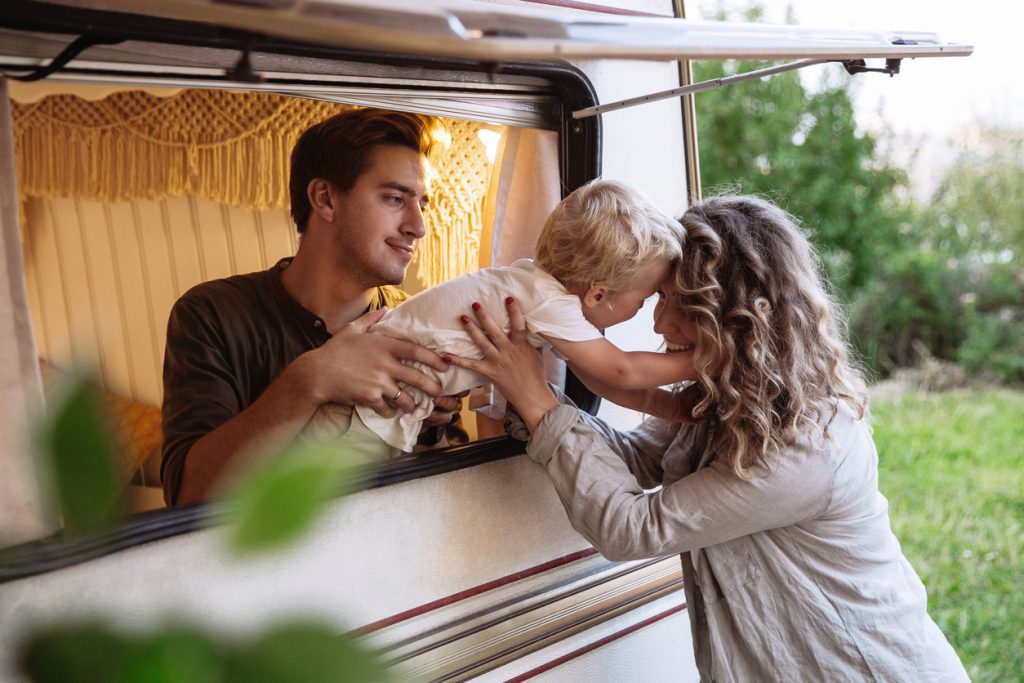 Family rv trip: young parents on vacation with little son living in motor house, modern camper trailer. Active family travel in caravan. Recreation lifestyle and summer vacation with kid in motor home