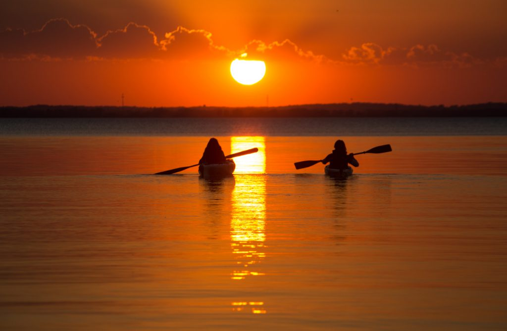 Great Lakes campgrounds - A beautiful sunset evening, two good friends, synchronized rowing, on the Bay of Green Bay in Wisconsin. These two kayaks were sitting on the mirror like water watching the sun drop in the western sky.